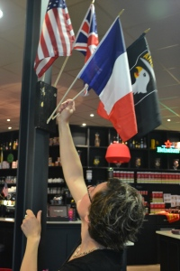 a-waitress-at-a-local-cafe-in-sainte-mere-eglise-france-hangs-a-flag-for-the-10