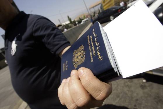 A Syrian man carries passports of relati